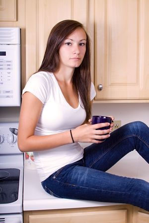 Teenager Girl Sitting on the Counter Drinking Coffee photo