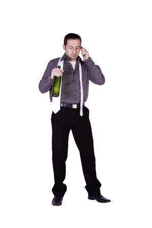 Isolated businessman celebrating with a bottle of drink while talking on the phone photo