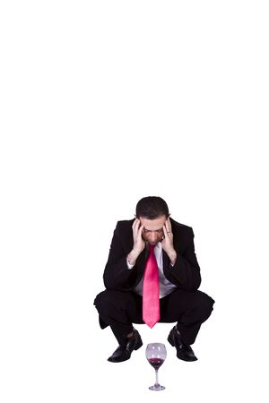 Crouched  Stressed Businessman Drinking - Isolated Background photo