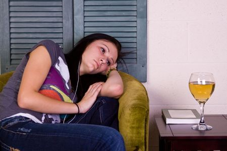 Teen Girl Falling Asleep while Reading a Book and Listening to Music photo