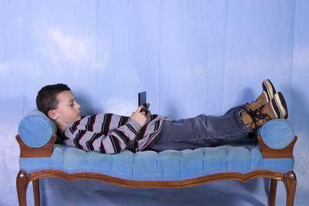 ni�os jugando videojuegos: Little Boy jugar al videojuego de mano en el Couch  Foto de archivo