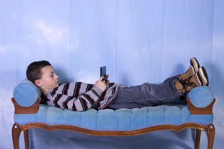 video gaming: Little Boy Playing Handheld Video Game on the Couch