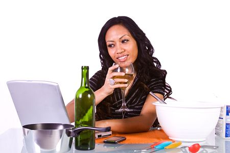 Beautiful Girl Preparing Food and Drinking Wine, Following A Recipe from the Internet Stock Photo - 6684095