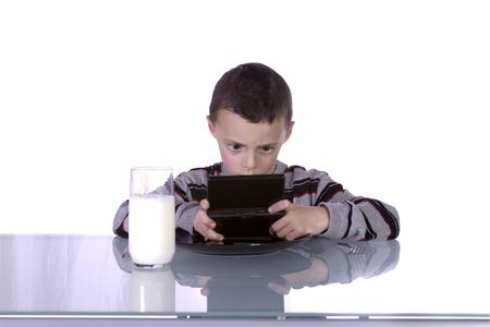 Little Boy Playing Handheld Video Game while Waiting for Dinner at the Table photo