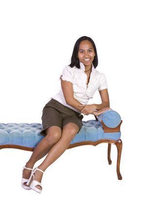 Woman sitting on a blue antique chair with white background photo