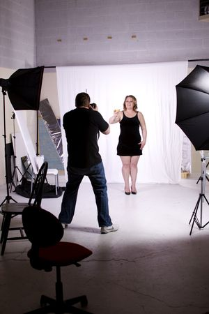 stock photography: Photographer Taking Pictures of a Model in the Studio