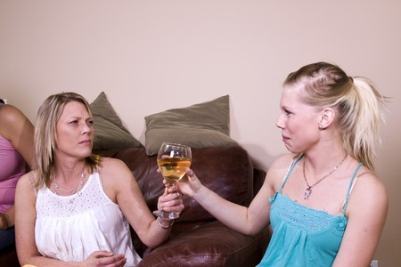 Mother Taking a Drink Away from Her Teenage Daughter photo