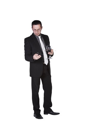 Isolated businessman celebrating with a glass of drink and a cigarette while talking on the phone photo