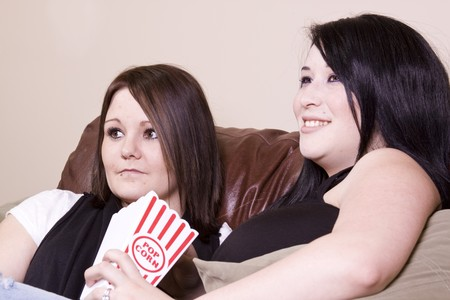 Two Girls Sitting on the Sofa Watching a Movie and Eating Pop Corn photo