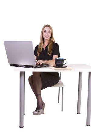 Isolated Businesswoman working on laptop with cup of coffee on her desk
