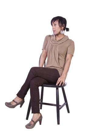 Mooie vrouw die zich voordeed op een stoel - geïsoleerde witte achtergrond Stockfoto