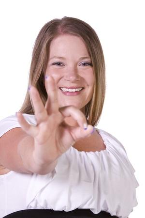 Tiro aislado de una bella joven dando el signo OK