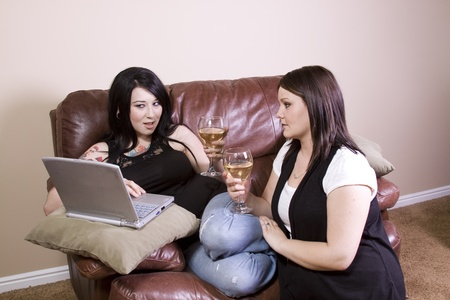 Two Girls at Home Sitting on the Couch with a Laptop photo