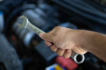Concept of engine maintenance. A technician is checking the level of the engine oil. Man holding white tissue paper to wipe the engine oil. Close up, Blurred background