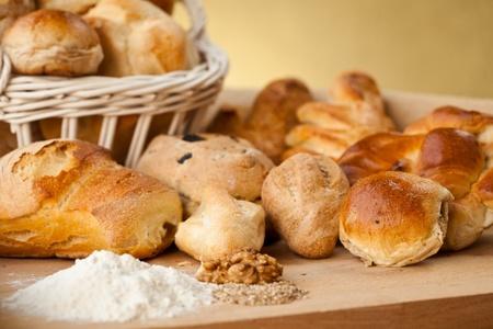 canasta de panes: Cesta de diferentes tipos de gourmet brerad con la harina, semillas de sésamo y frutos secos Foto de archivo