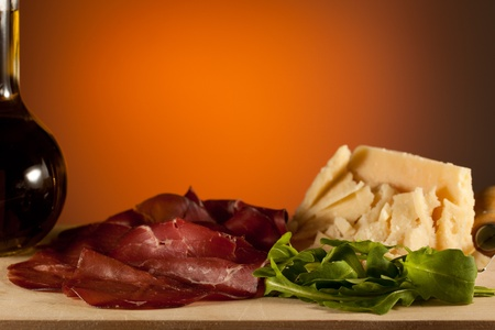Sliced bresaola ham with salad and parmesan cheese with an oil bottle, over a wooden chunk-board photo