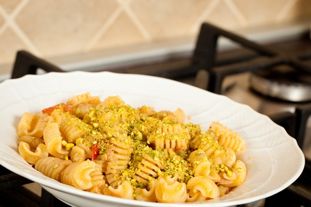 A dish of pasta with salmon, tomatoes and pistachios nuts Stock Photo