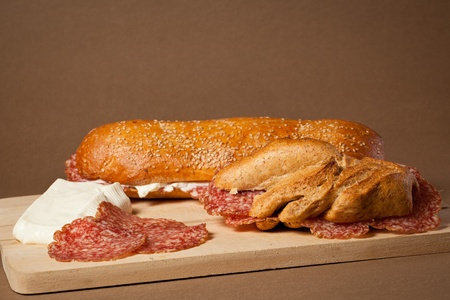 Two sandwiches wit italian sliced salami and fresh cheese over a wooden board Stock Photo