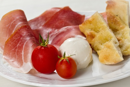 Dish with typical Italian food. Raw ham, mozzarella cheese, cherry tomatoes and focaccia pizza photo