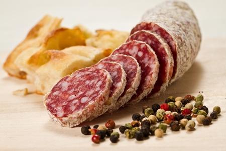 sliced salami with focaccia pizza and peppergrain over a wooden chunkboard Archivio Fotografico