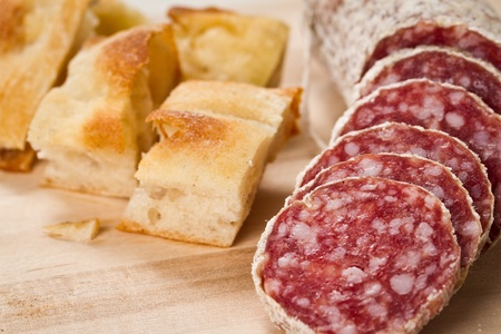 sliced salami with focaccia pizza over a wooden chunkboard