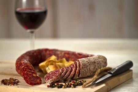 Salami and spicy salami with focaccia pizza decorated with  peppergrain and grounded red pepper over a wooden chunk-board. With a red wine glass on background photo