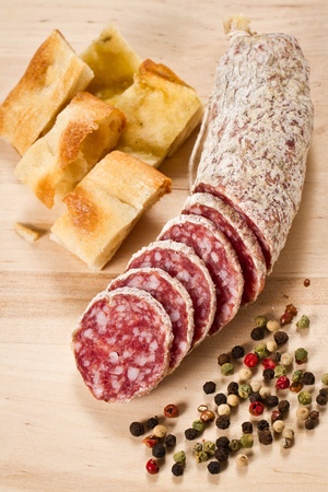 sliced salami with focaccia pizza and peppergrain over a wooden chunkboard Stock Photo - 11195179