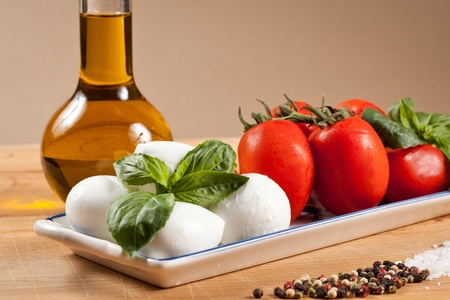 caprese: Mozzarella cheese bits and cherry tomatoes with basil leaf. Healty caprese salad with oil bottle, salt and pepper