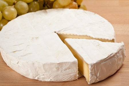 bree cheese with a slice off and stalkes of grapes in isolated studio shot over whooden background