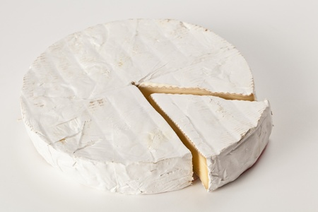 bree cheese with a slice off in isolated studio shot over a white background