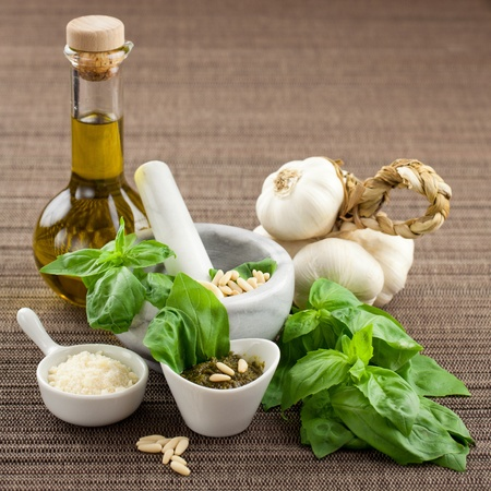 Bowl of pesto genovese sauce with ingredients. oil, parmesan cheese, garlic, pine nuts and basil photo
