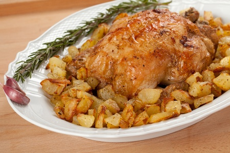 Roasted chicken with potatoes in a white plate decorated with garlic and rosemary over a wooden board