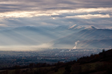 broken through: Avezzano town in a foggy day lighted with few sun ray broken through the clouds Stock Photo