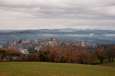 orte: View of rural village of Orte in a misty morning with seeded fields in foreground Stock Photo