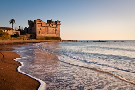 View of Pyrgi castle in Italy with calm sea and foamy waves on brown sand photo