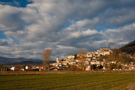 Cultivated field below Scurcola Marsicana village in Italy with a dramatic sky