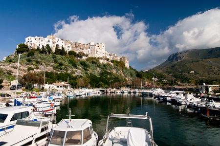 View of Sperlonga harbor wit boat docked and village in background Archivio Fotografico