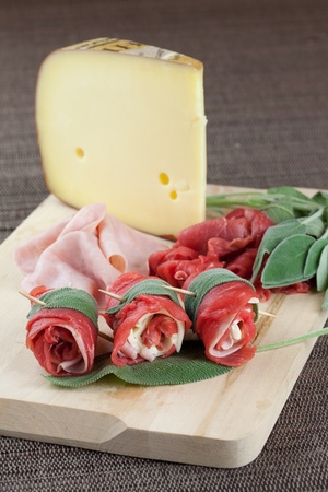 uncooked beef rolls with ham and cheese with raw ingredients over a wood board