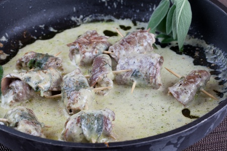 Cooked beef rolls with ham and cheese still in the pan with a creamy sauce