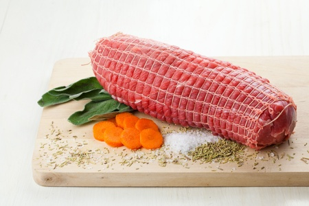 Raw meet roll with sage, carrots, rosemary and salt, over a wood board and ready to be roasted