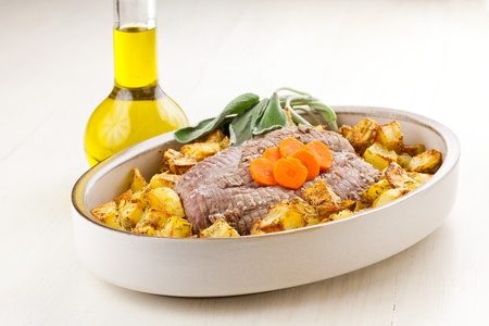 Roasted  meet and potatoes with sage and carrots garnish in dish over a white wood table and an oil bottle on side