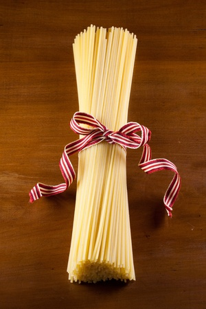 fine raw spaghetti pasta tighten with cotton ribbon over an antique wood table