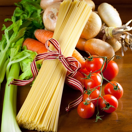 raw spaghetti pasta and ingredients for tomato sauce over an antique wood table Archivio Fotografico