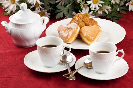 Two coffee cup and two heart shaped pastry over a red table cloth with daisies bouquet in background