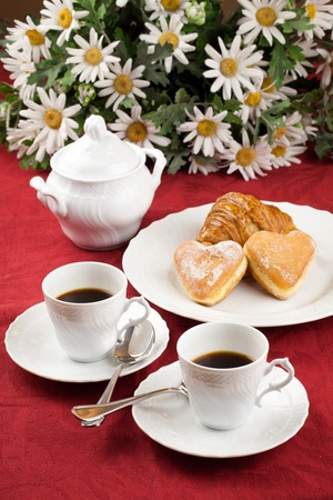 Two coffee cup and two heart shaped pastry over a red table cloth with daisies bouquet in background photo