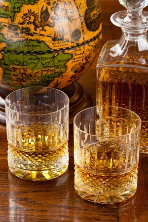 Fine scotch whisky in crystal bottle and tumbler glasses over a wood antique table with an old globe in background Stock Photo - 11551081