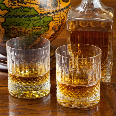 Fine bourbon whiskey in crystal bottle and tumbler glasses over a wood antique table with an old globe in background
