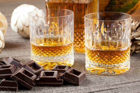 tumbler: Dark chocolate and fine burbon whiskey in crystal bottle and tumbler glasses with stylish spheres and antique globe in background Stock Photo