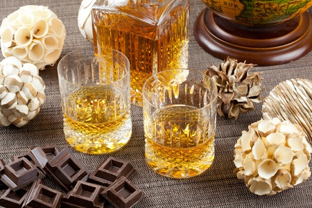 Dark chocolate and fine scotch whisky in crystal bottle and tumbler glasses with stylish spheres and antique globe in background Stock Photo