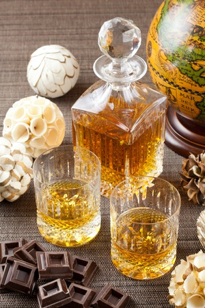 Dark chocolate and fine whiskey in crystal bottle and tumbler glasses with stylish spheres and antique globe in background photo